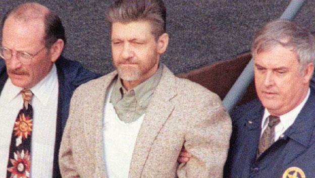 Ted Kaczynski, l'Unabomber, au centre de l'image entouré de 2 fédéraux.