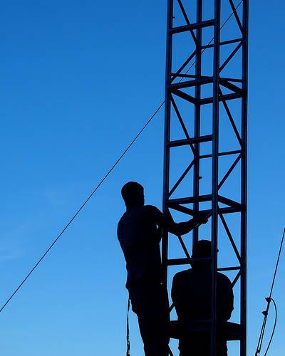 Homme gravissant une échelle sur fond de ciel bleu.