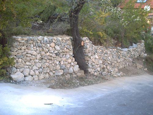 Mur en pierres de récupérations en cours