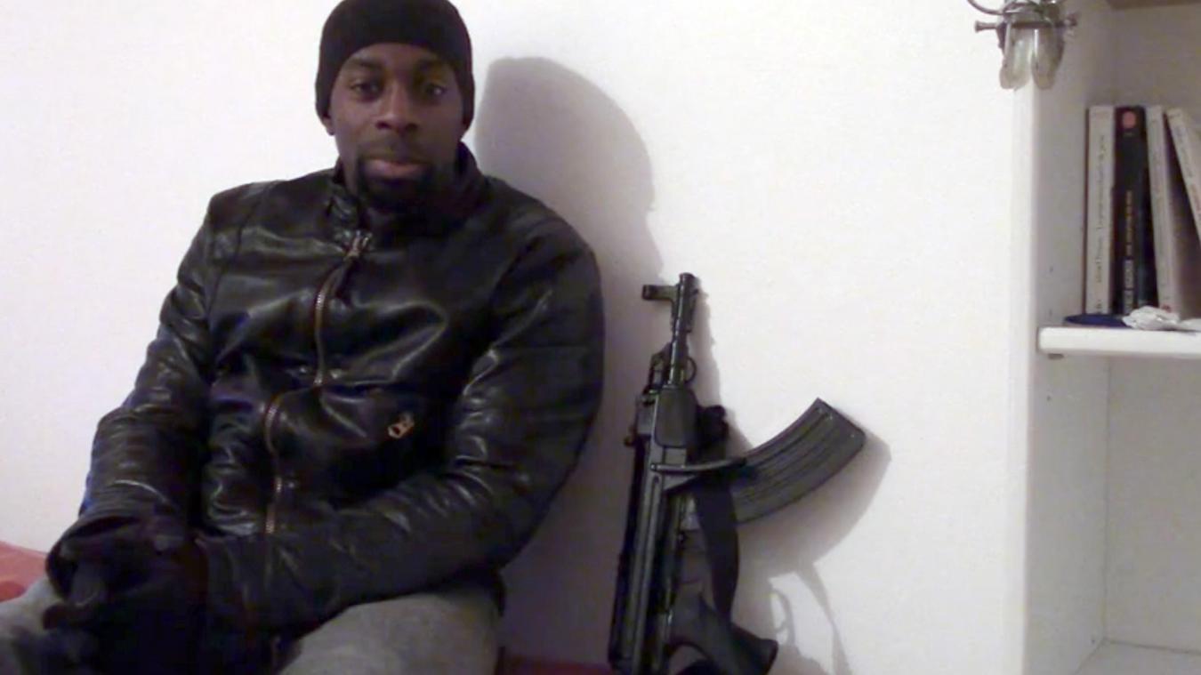 Amedy Coulibaly devant sa bibliothèque. Extrait de la vidéo de revendication des attentats du 7 et 9 janvier 2015 contre Charlie Hebdo (Le Greffier Noir)