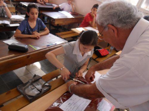 Le Président du centre aide la candidate à ouvrir le sac cantenant les sujets