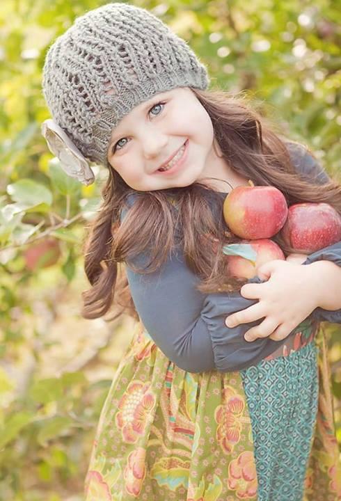 petite-fille-souriante-tete-penchee-bonnet-pommes-dans-les-bras-nature.jpg