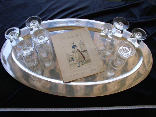Enorme plateau en métal argenté (longueur 80cm) marqué du sigle de la Cie Générale Transatlantique, accompagné de 8 verres et du menu des 1ères du 20 Septembre 1936, origine paquebot Normandie, ensemble rare et en bon état, verres à l'état de neuf siglés