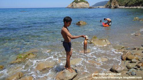 Un enfant  chassant  un  poulpe   au bord de la plage