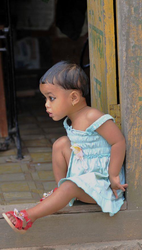 une petite fille sur un pas de porte
