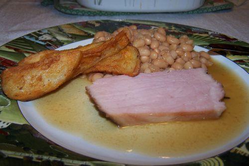 Fèves et jambonneau , à l ' assiette , accompagnés de pommes de terre frites et de crudités déjà avalées donc invisibles !