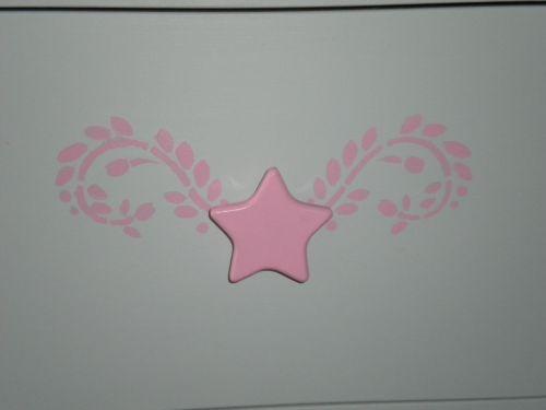pochoir rose sur le tiroir du milieu de la commode