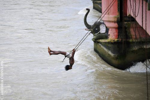 A young boy acrobatically swings from a bridge - Haridwar