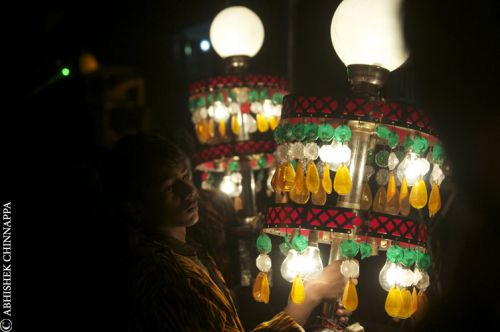 A young boy carries ornemental lights to welcome the bride groom during a wedding - Rishikesh