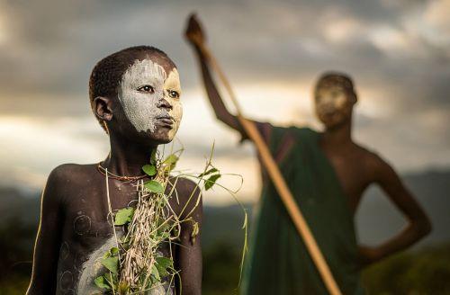 Un garçon de la tribu nomade suri en Éthiopie, avec la tenue traditionnelle et le visage et le corps peints