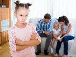 enfant_triste_avec_un_autre_enfant_choye_par_les_parents_en_arriere_plan.jpg