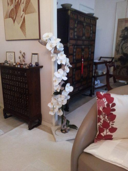 Grande orchidée grimpant sur ratan blanchi, fixé sur un socle imitation pierre. Livré et installé chez le client.