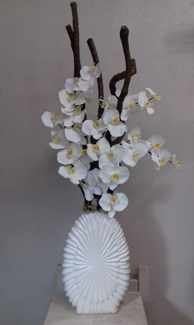 Orchidées blanches et bois dans grand vase blanc. Hauteur 105cm.