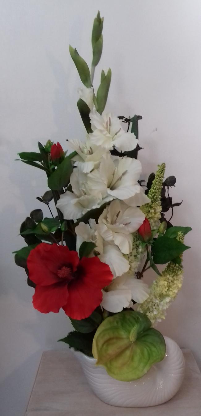 Coupe escargot avec hibiscus, glaïeul, anthurium, graminées et feuilles d'eucalyptus. Hauteur 67 cm.