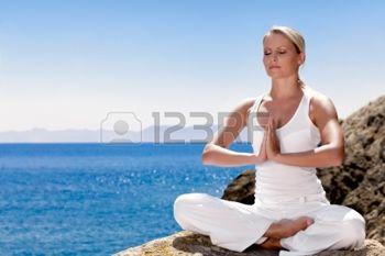 12508307-belle-fille-v-tements-positif-dans-sit-blanc--bord-de-la-mer-sur-la-roche-et-la-m-ditation-dans-le-y.jpg