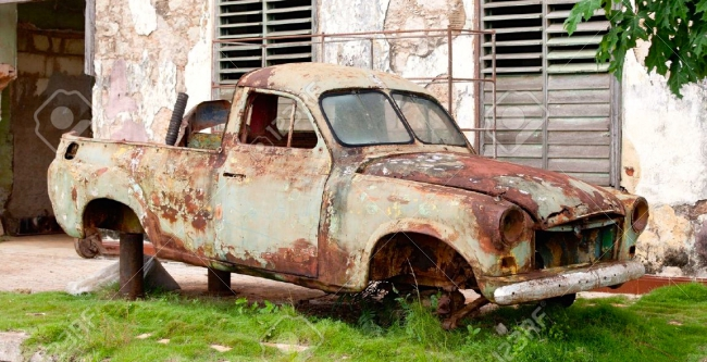 9062305-Very-old-car-wreck-rusty-and-scrapped-in-front-of-old-house-Stock-Photo.jpg