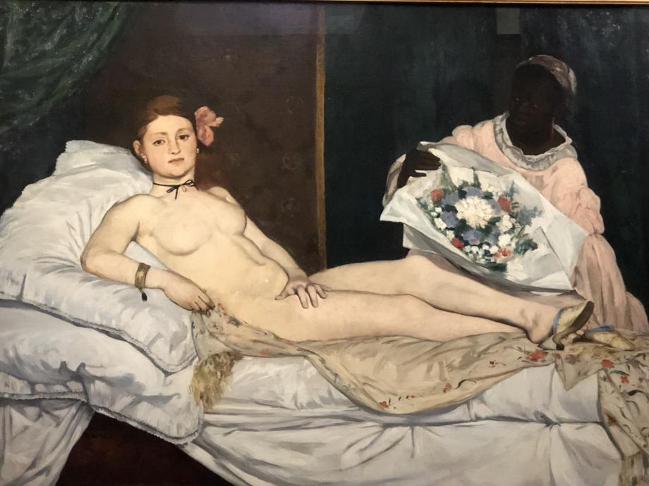 Le tableau a été exposé en 1865 au Salon et a provoqué un scandale retentissant. Mais la servante noir est passée relativement inaperçue hormis quelques caricatures violentes qui l'ont prise pour cible. Elle est représentée comme une servante, portant des fleurs. Mais la part subversive du tableau est représentée par la courtisane