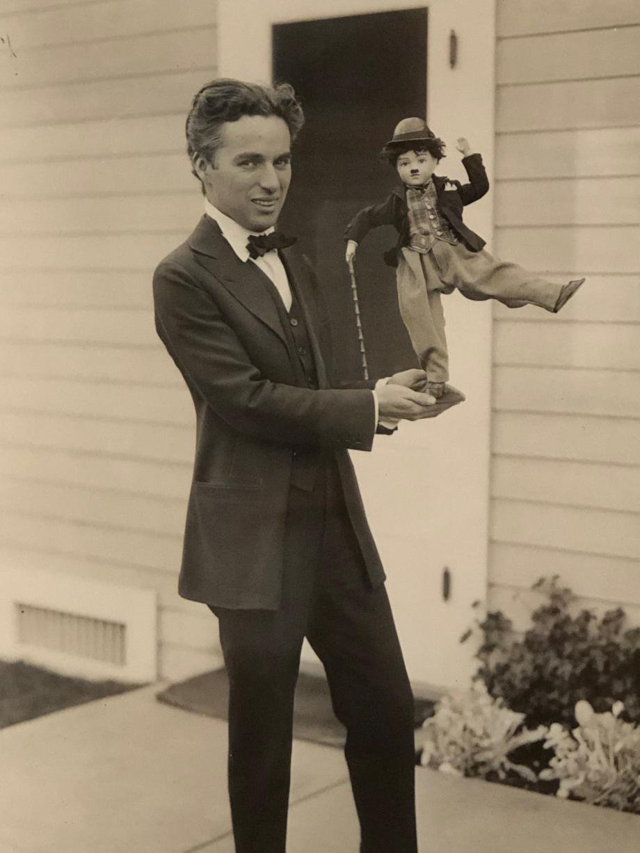 Chaplin posant avec une poupée à l'effigie de Charlot vers 1920