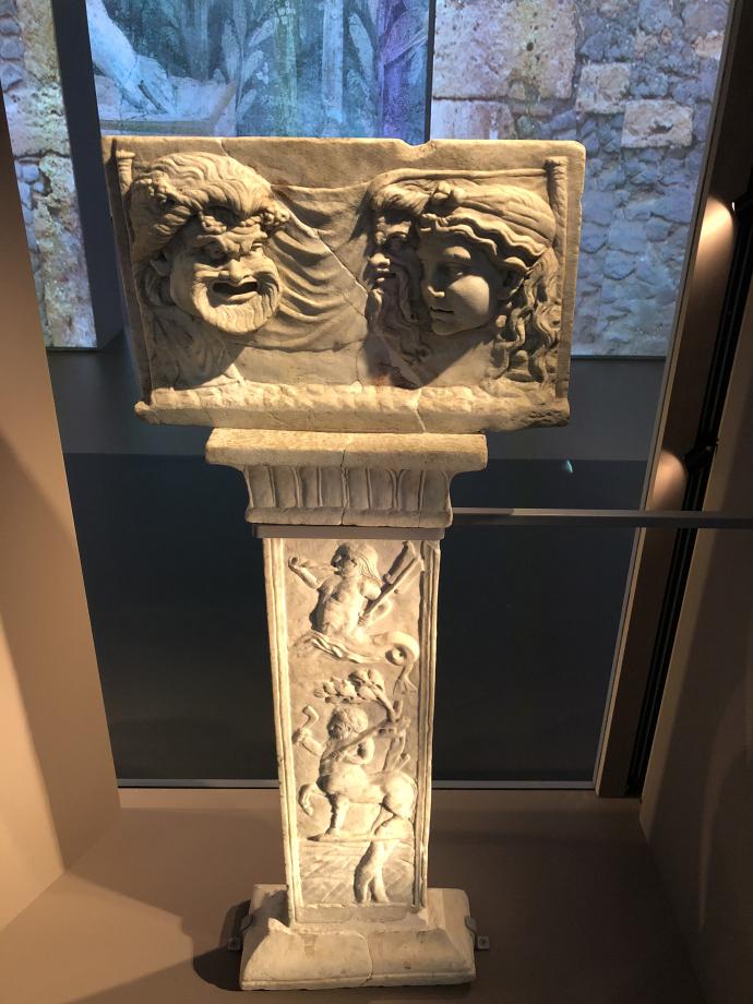 Plaque votive décorée en relief avec masques de théâtre sur petits pilastres aux motifs végétaux Maison des Amours dorés, jardin