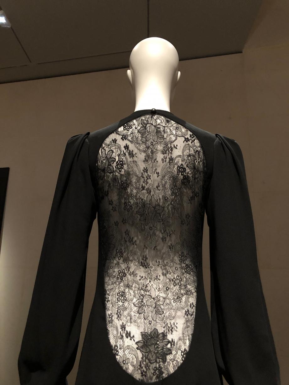 Le devant de la robe, austère, est boutonné très haut, le dos est impudiquement voilé d'une dentelle de soie Chantilly de la nuque à la naissance des reins
