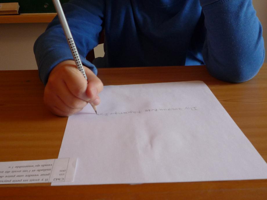 Yoan, au début de la rééducation. Le crayon est vertical, le pouce gêne le mouvement des doigts, la feuille est droite, pas tenue, et Yoan commence à écrire au milieu...