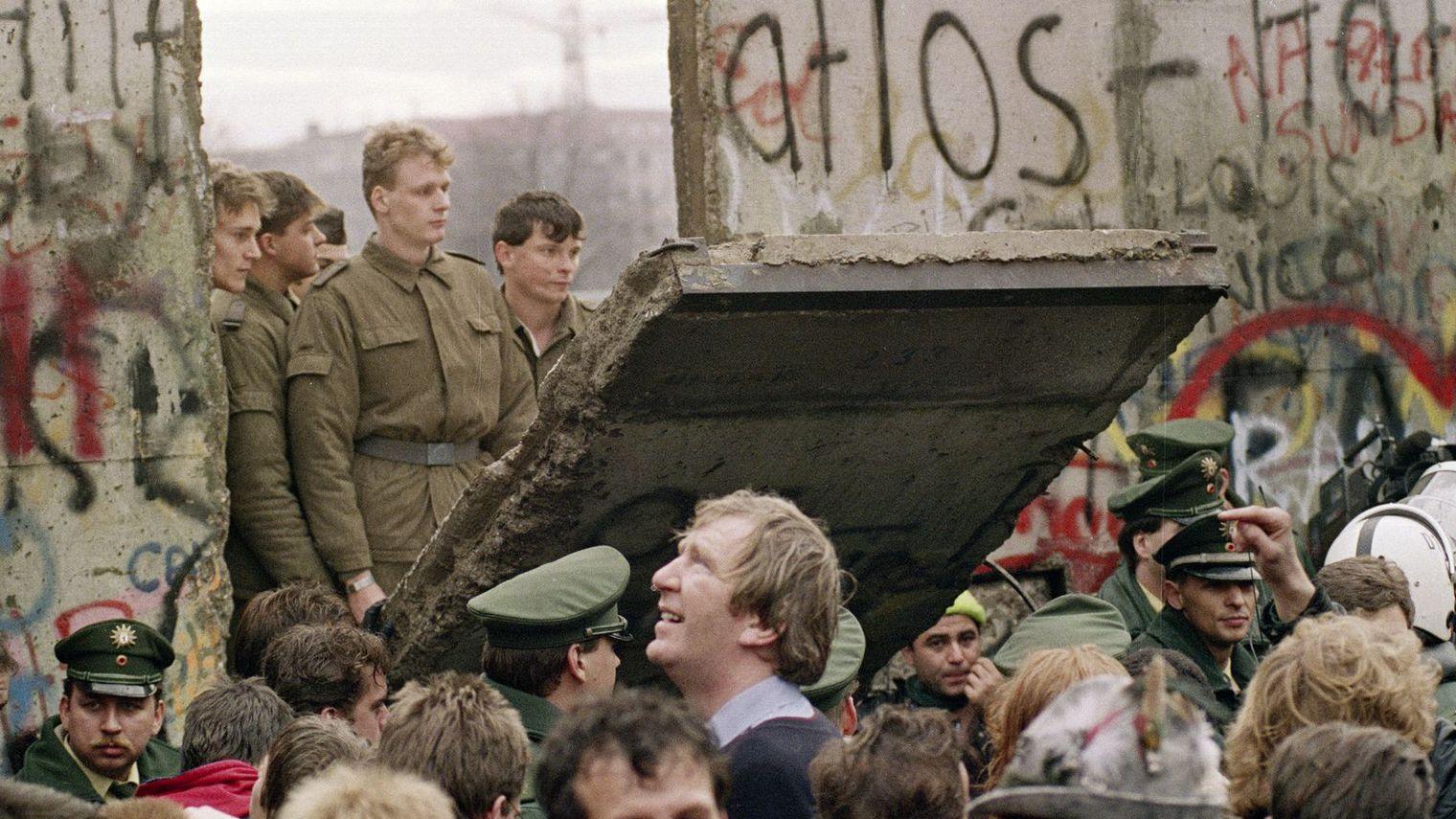 des-allemands-de-l-ouest-se-pressent-devant-le-mur-de-berlin-le-11-novembre-1989-regardant-des-gardes-frontiere-est-allemands-ouvrant-une-breche-dans-l-ouvrage-pres-de-.jpg